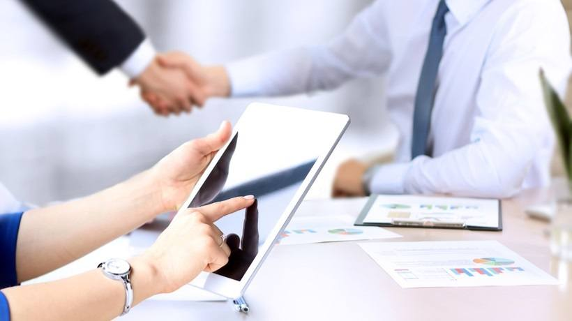 person pointing at tablet with people in background shaking hands