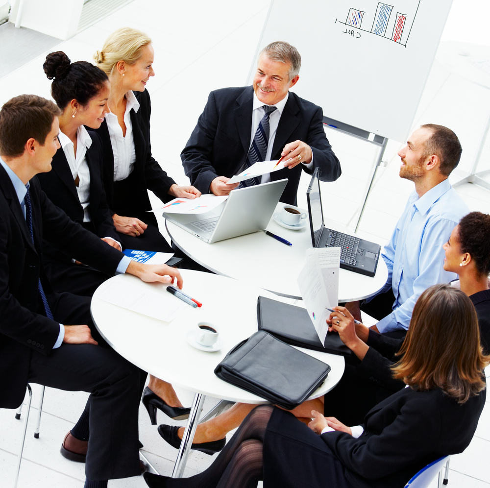 smiling men and women in suits looking at each other around a table with laptops