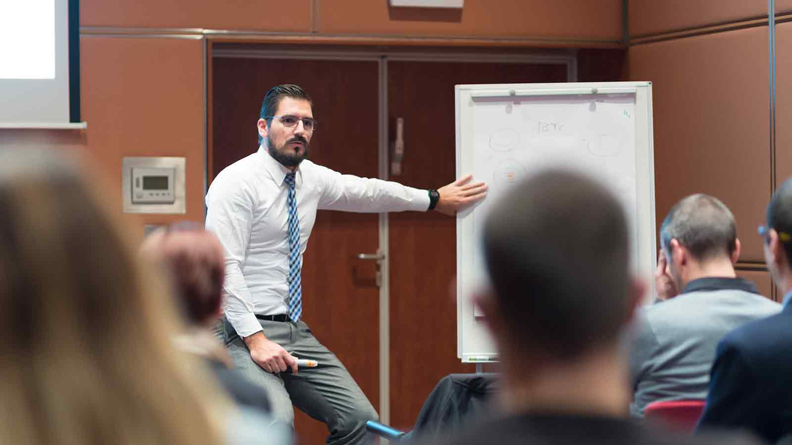man pointing at white board in front of small group