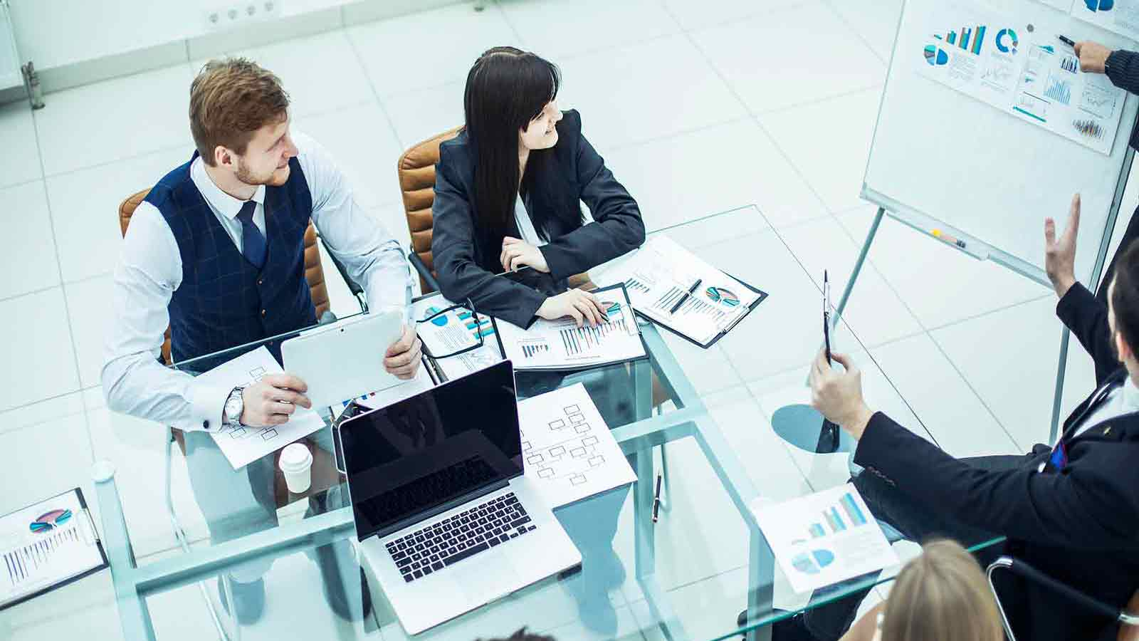 man and women in suits sitting at table looking at a person presenting planning charts