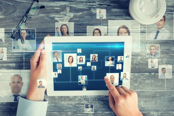 hands touching a tablet screen with headshots of people in a network