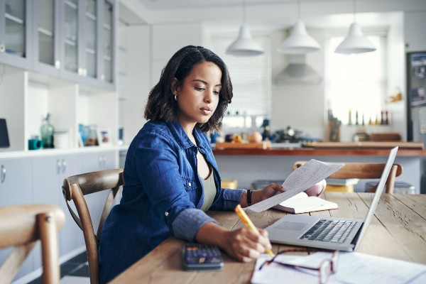 woman working at home on kitchen table with laptop open and she's holding paperwork