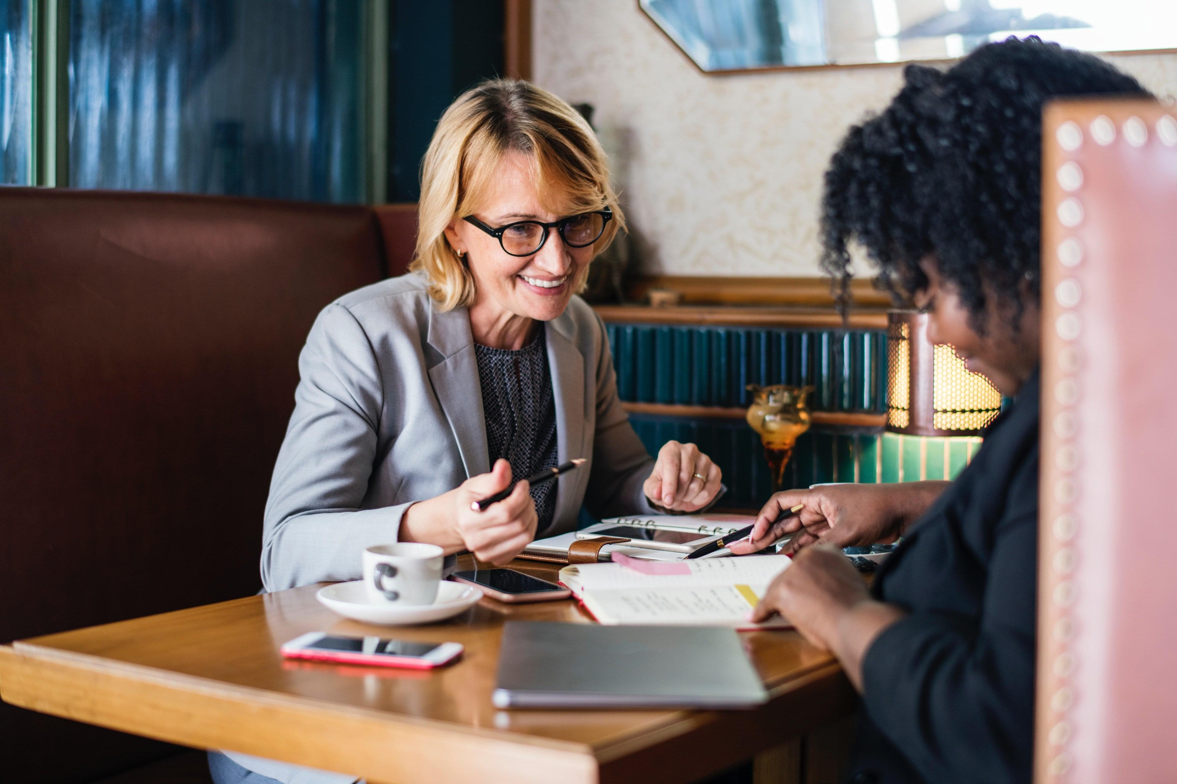 Business development meeting with two women at restaurant booth