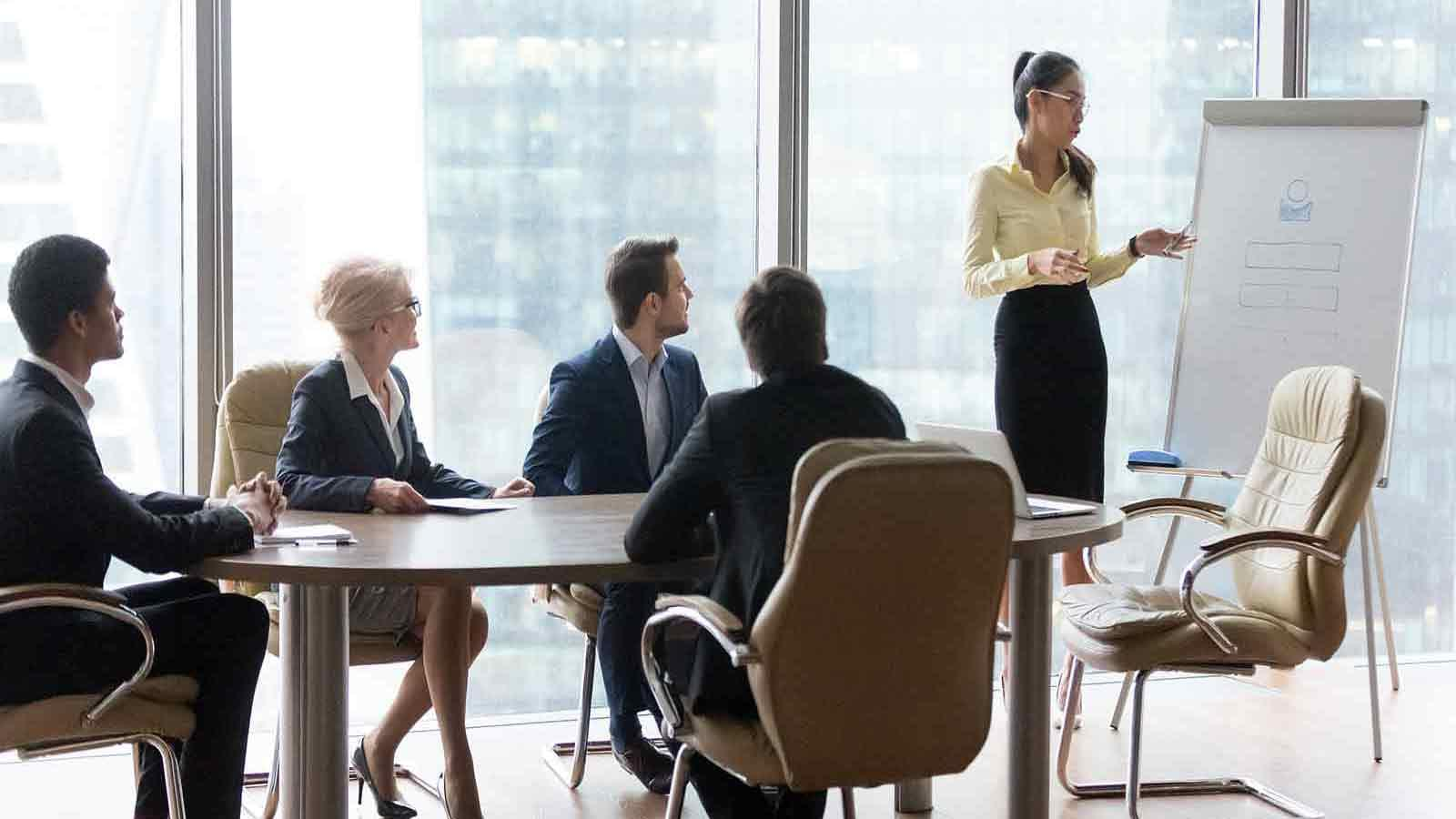 people in suits at table looking at woman presenting materials on whiteboard