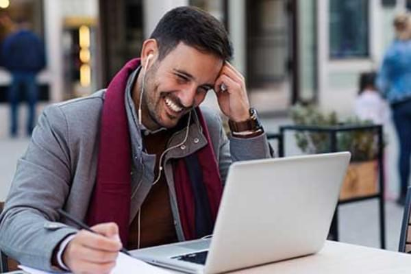 man working on laptop on a public table with earbuds in speaking to friend through computer