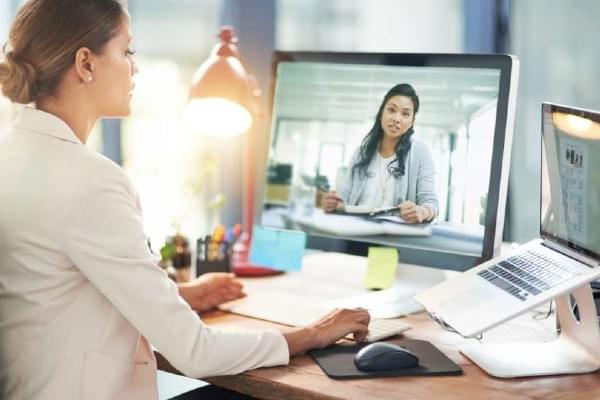woman working at desk and speaking through video conference call with another woman