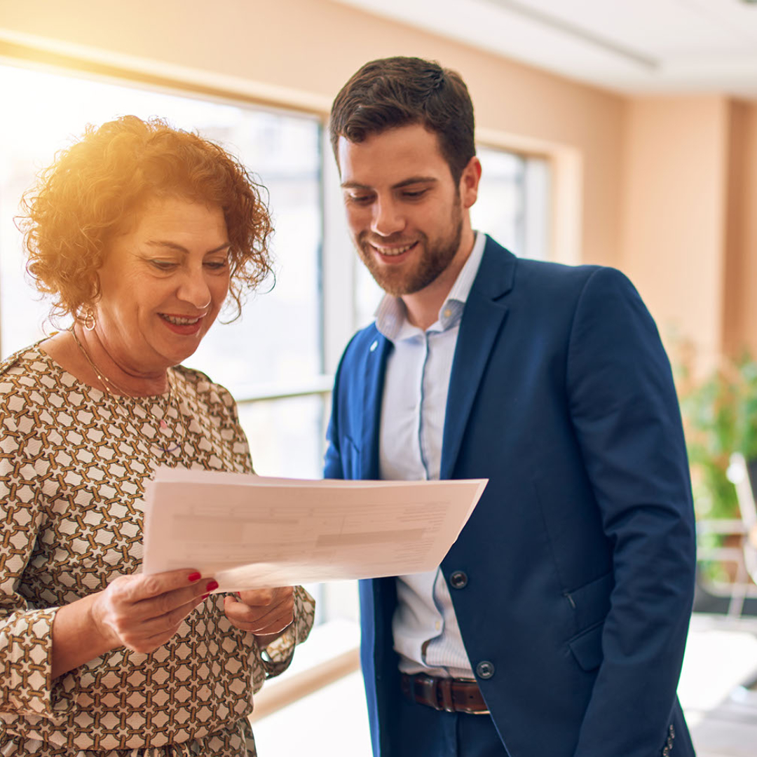 Middle aged business woman going over sales pipeline with young business man