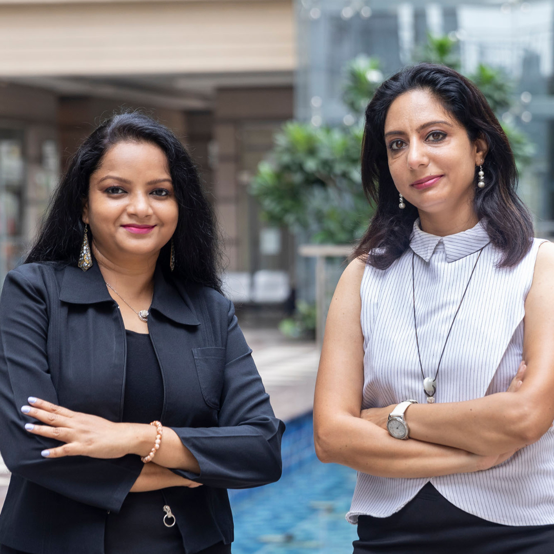 Two indian female business executives standing outside in front of office building. CMO and CEO