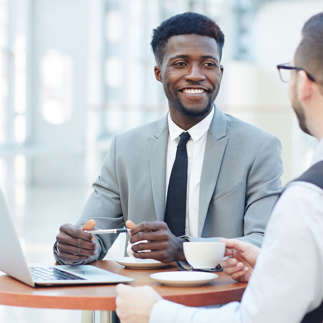 african american man speaking with colleague in office; business coaching session